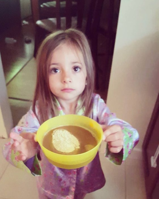 niña sosteniendo un tazón con café