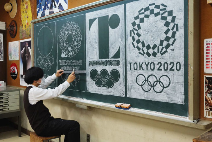 maestro dibujando logo de juegos olímpicos en pizarrón