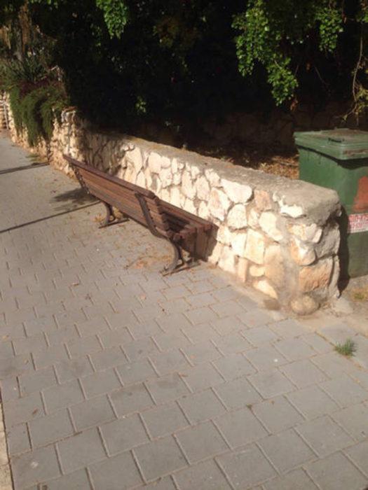 banca frente a un muro de piedra