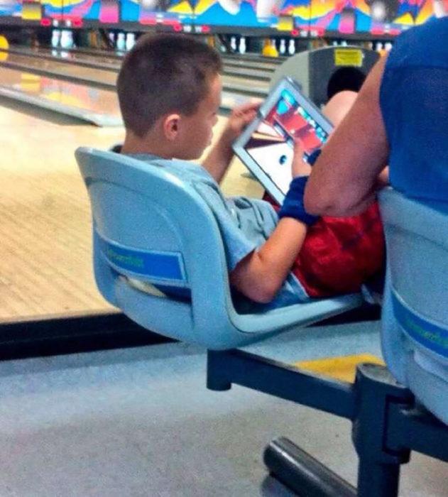 niño jugando boliche en su tableta electrónica en un establecimiento de boliche