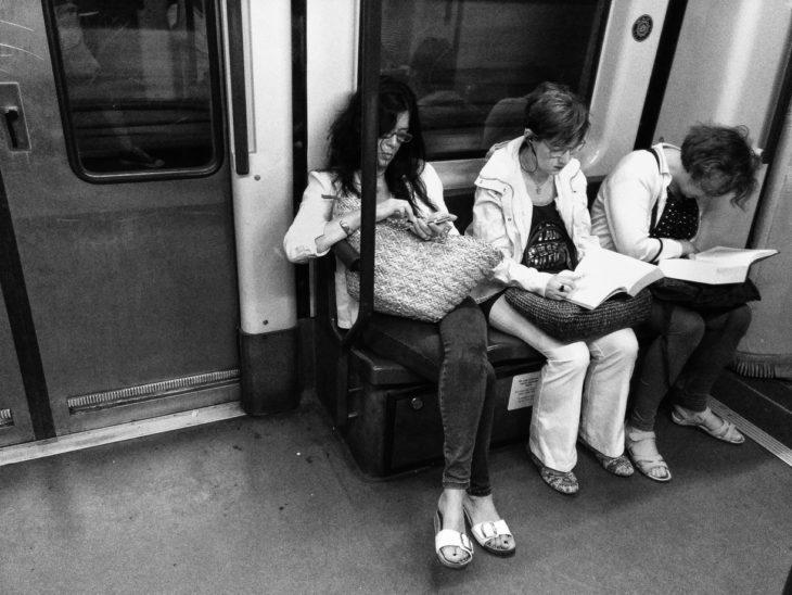 foto a blanco y negro personas leyendo en el metro