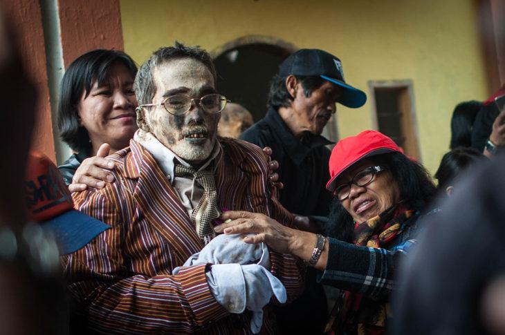 personas sostienen a momia vestida con ropa nueva