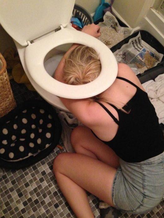 Foto de chica en shorts vomitando después de una borrachera