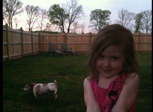 Animales photobomb - Niña en una foto mientras su perro orina atrás