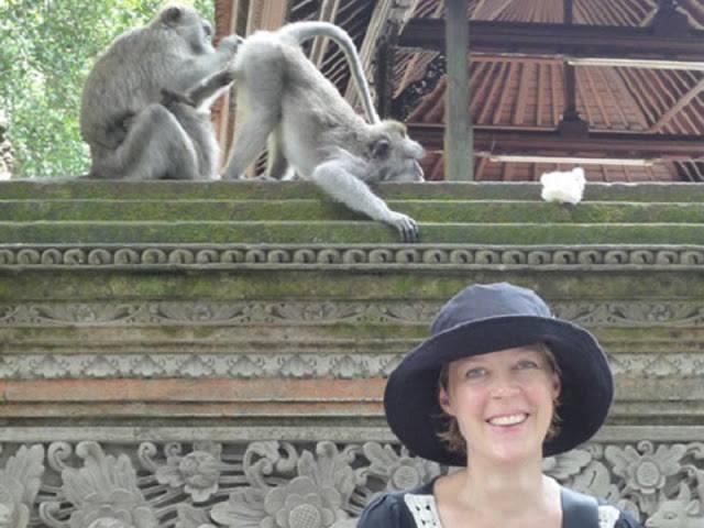 Animales photobomb - mujer en una foto y atrás salen dos monos, uno de ellos le está viendo el trasero al otro