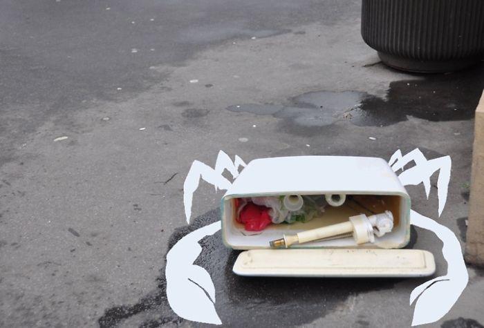 Arte en las calles de París - un cangrejo en la basura