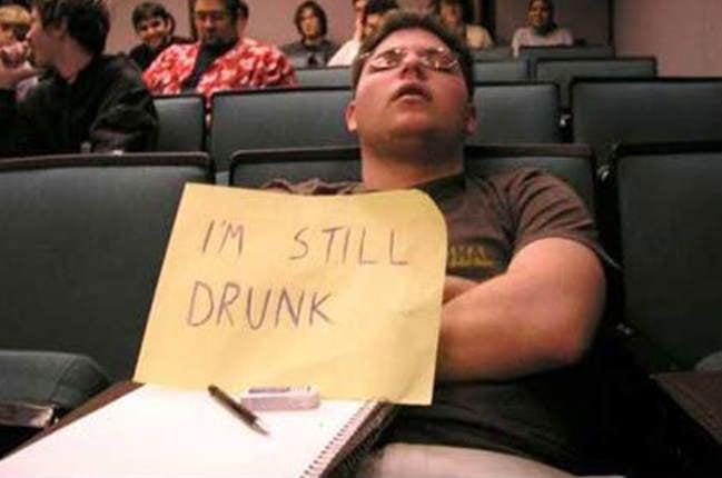 Estudiante dormido con un letrero que dice sigo borracho
