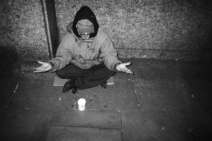 vagabundo meditando dsobre el asfalto frío de Londres