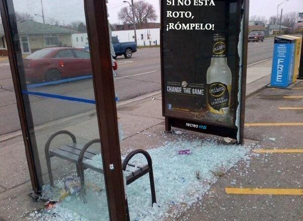 Publicidad de alcohol que cie si no está roto rómpelo, y alguien rompió la vitrina