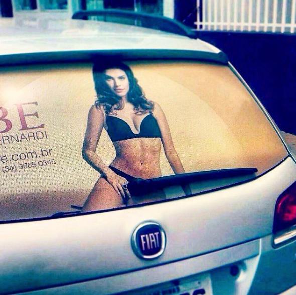 Publicidad de mujer en ropa interior en el vidrio de atrás de carro, el limpiaparabrisas queda en un lugar inapropiado