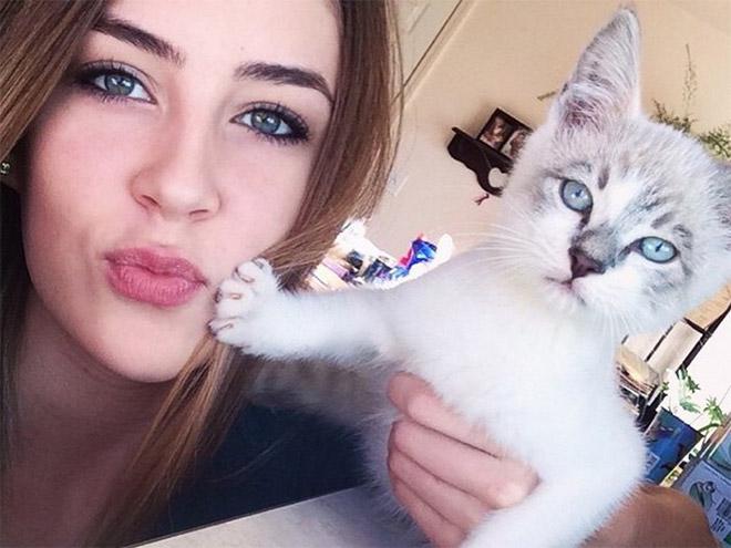 mujer de bellos ojos junto a su gato gruñon