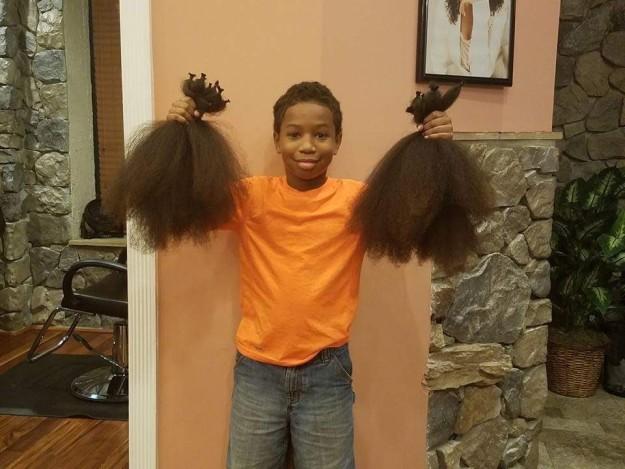 Niño dona su cabello - sosteniendo los dos mechones