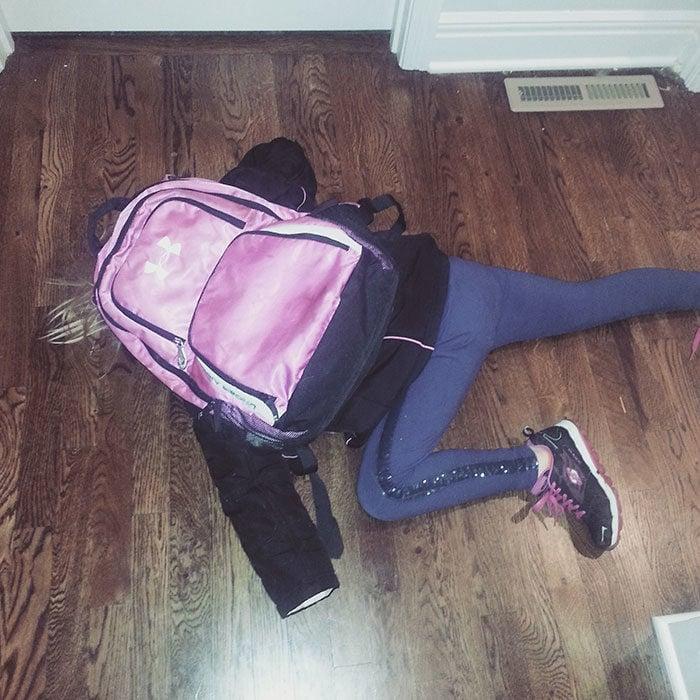 Niña tirada en el piso con su mochila
