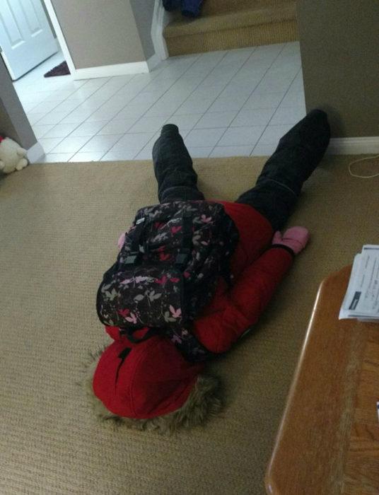 Niña con sudadera roja cansada tirada en el piso de su casa