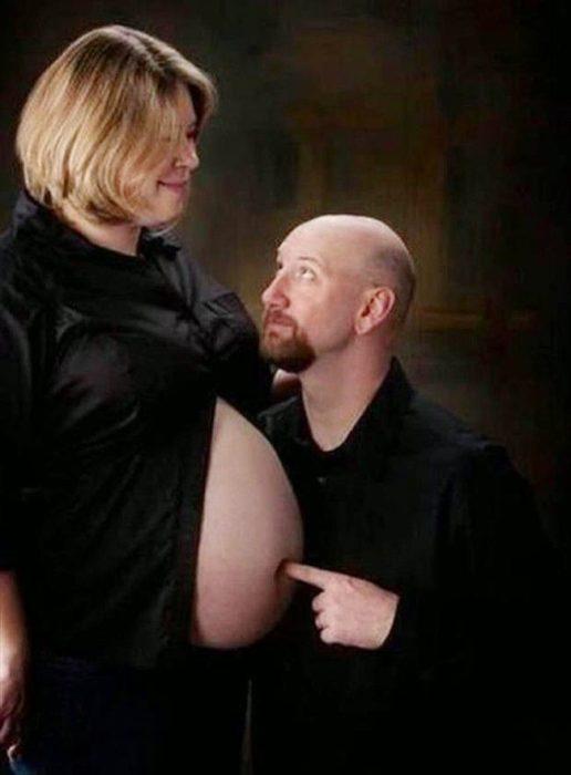Las peores fotos embarazo - Hombre metiendo su dedo en el ombligo de la mujer