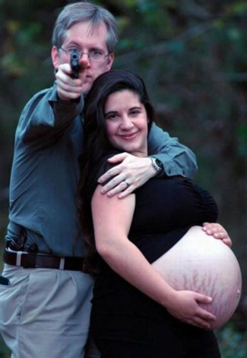 Las peores fotos embarazo - Mujer sonríe mientras hombre apunta a la cámara con una pistola