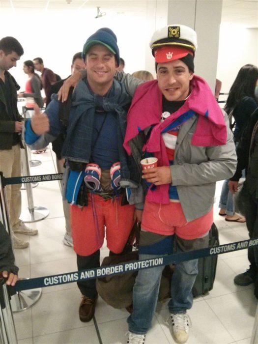 Dos hombres con toda su ropa puesta y una maleta chica