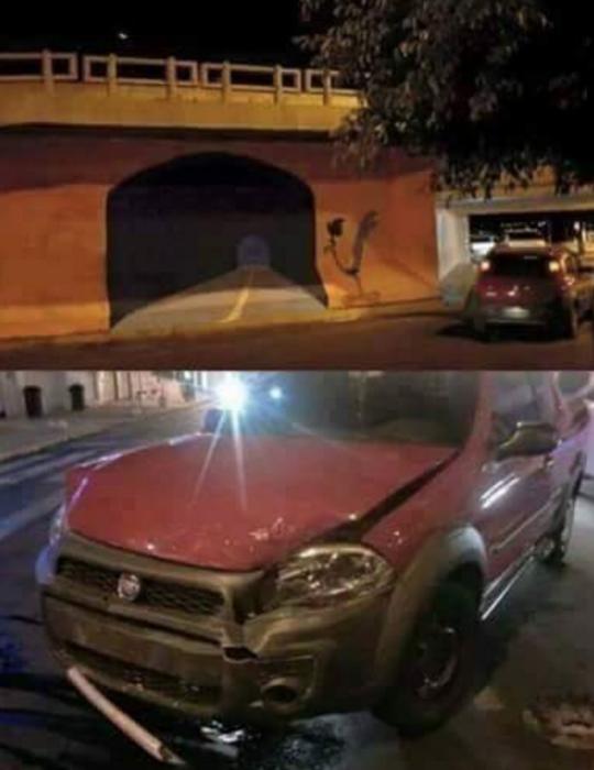 Grafiti en un muro de un puente. Al lado un carro chocado