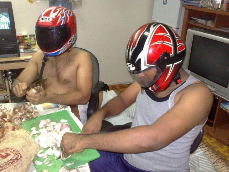 Dos hombres con casco de motociclistas mientras cortan cebolla