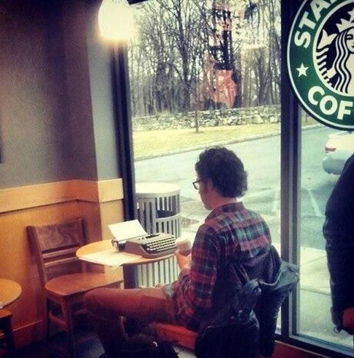 Hombre en cafetería con su máquina de escribir