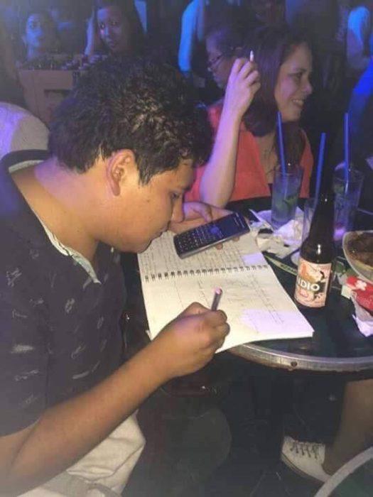 Chico en un bar haciedno la tarea