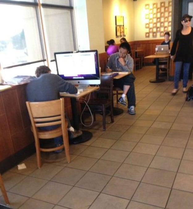 Hombre en cafetería con su computadora de escritorio