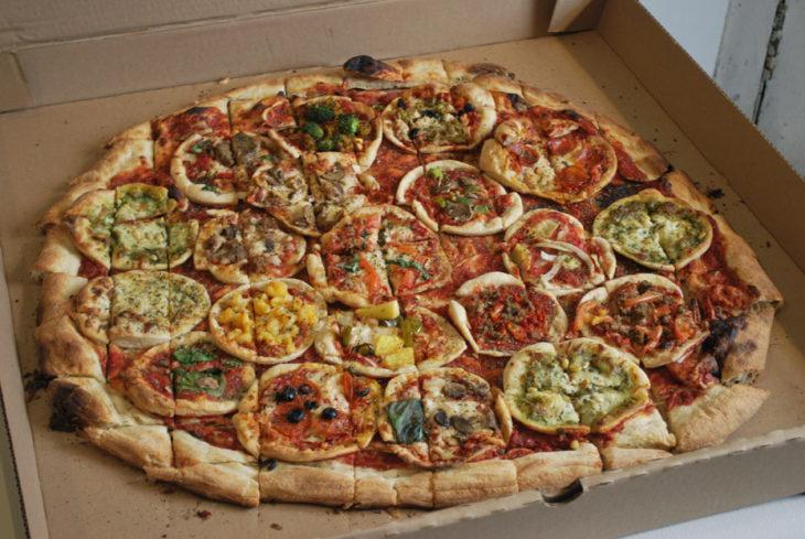 Una pizza grande con muchas pizzas chicas en su interior