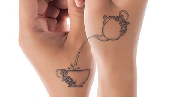 Tatuaje en una mano de una tetera sirviendo café y en la otra mano de la taza de café donde está cayendo