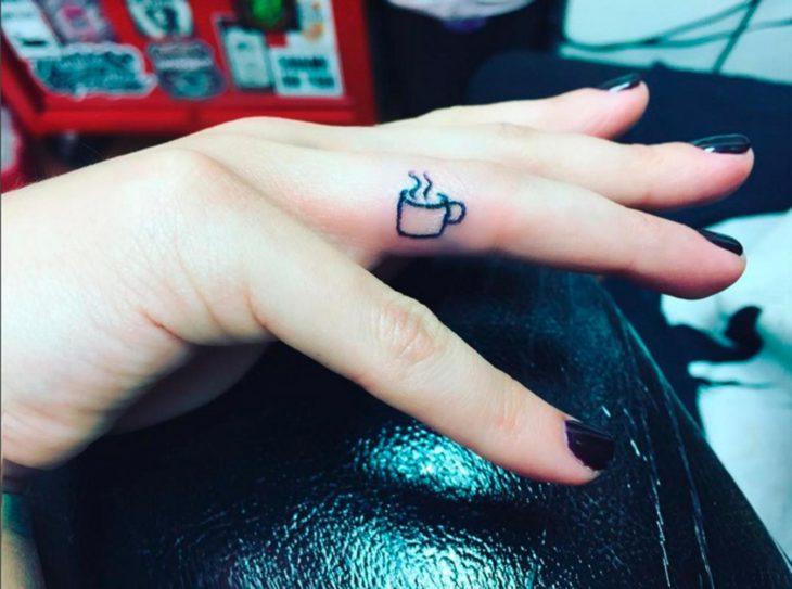 Tatuaje en el dedo de una mini taza de café