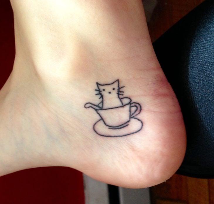 Tatuaje de una taza de café con un gatito adentro