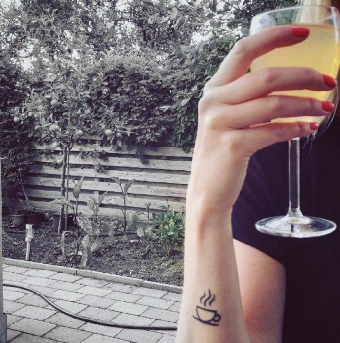 Tatuaje de una taza de café en el antebrazo