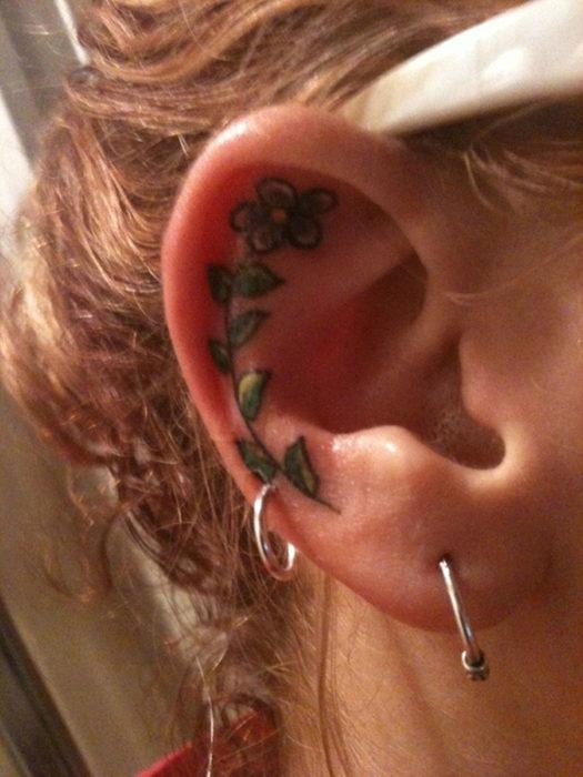Tatuaje de una flor larga adentro del oído