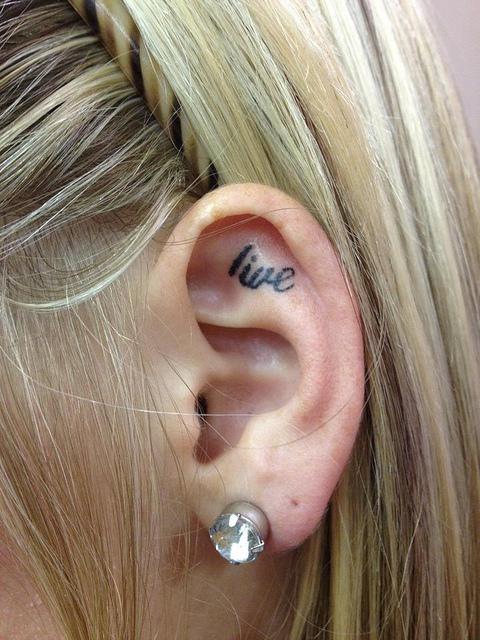 Tatuaje con la palabra live adentro del oído