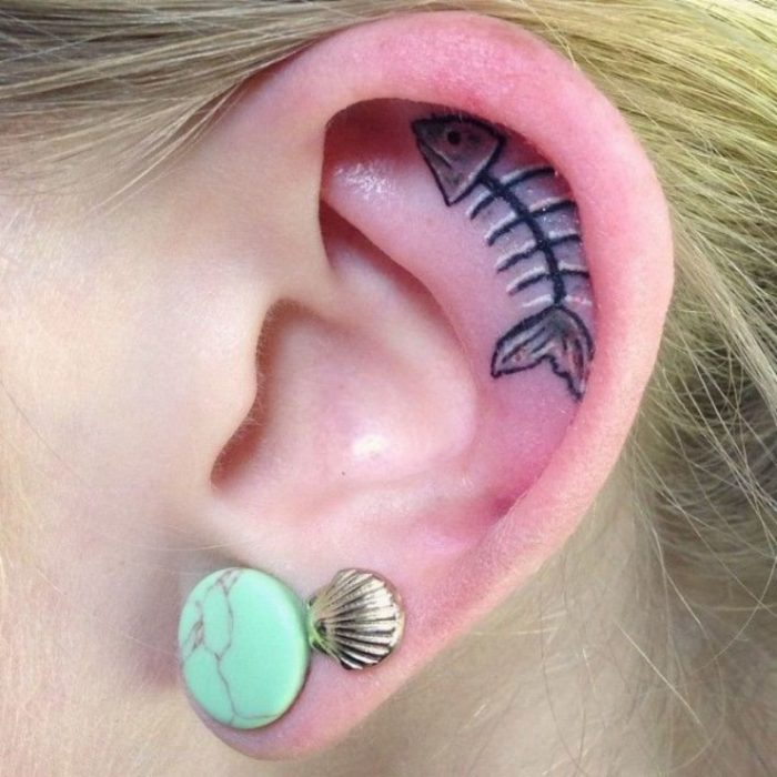 Tatuaje del esqueleto de un pez adentro del oído