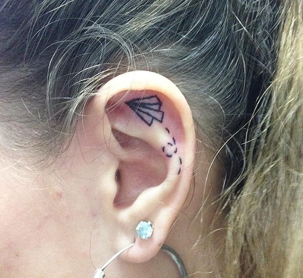 Tatuaje de un avión de papel adentro del oído