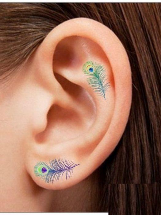 Tatuaje de pluma de pavorreal adentro del oído