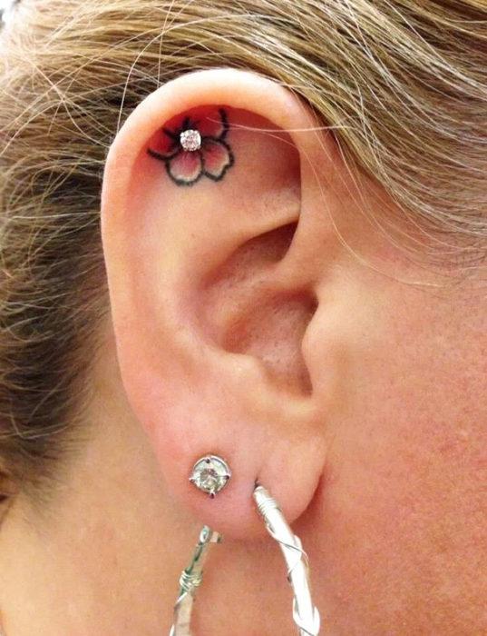 Tatuaje de una flor adentro del oído