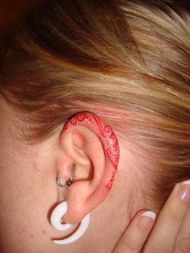 Tatuaje rojo en el oído
