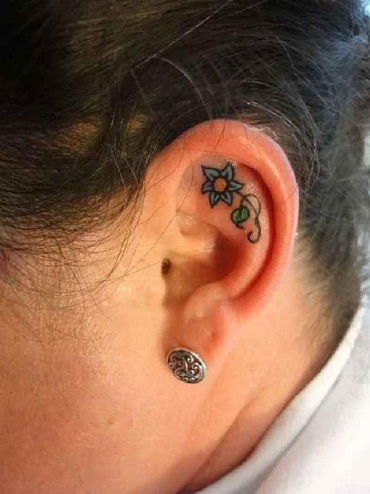 Tatuaje de una flor azul adentro del oído