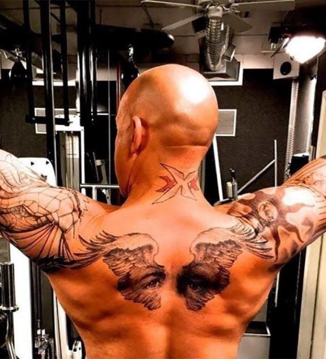 Vin Diesel ejercitándose. Se ve un tatuaje de unas alas y una mirada en su espalda