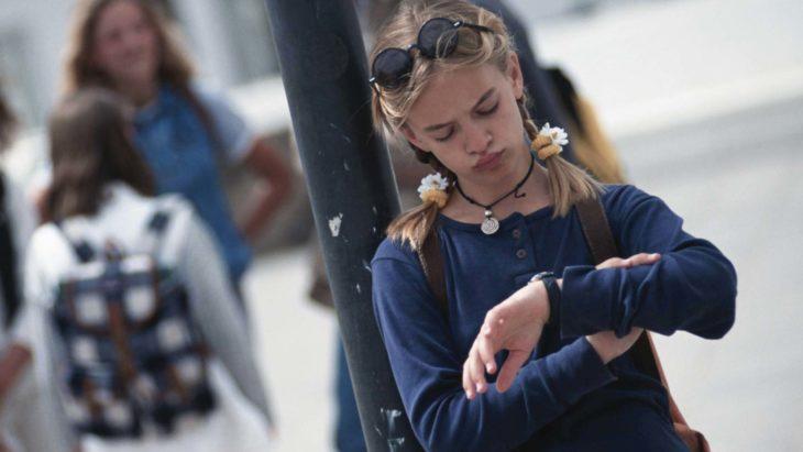 muchacha mirando su reloj