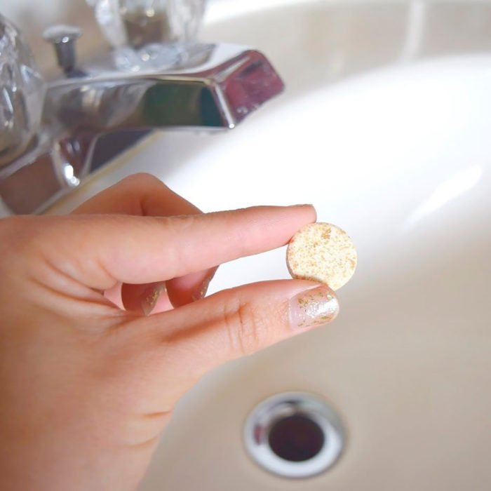 mano sosteniendo pastilla sobre un lavabo