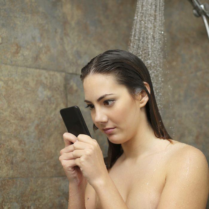 persona en la ducha con el celular
