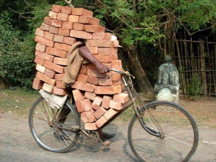 señor en bicicleta cargando con ladrillos