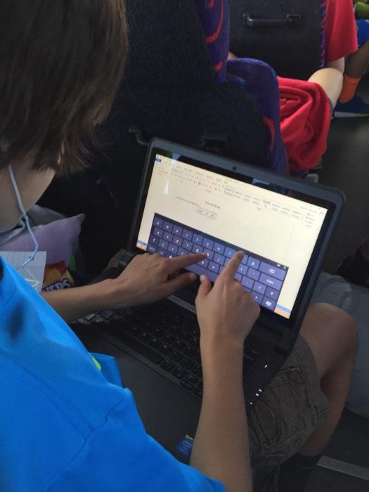 chico tratando de escribir en la pantalla de su laptop