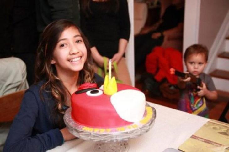 niña sonriendo con su pastel mientras su hermano le apunta con una pistola de juguete