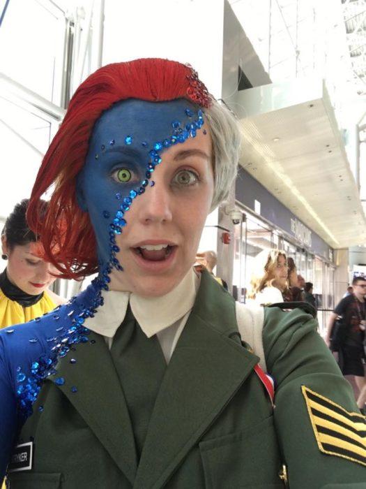 mujer con la mitad de su cara pintada azul y mita de peluca blanca y otra mitad roja haciendo gesto de sorprendida