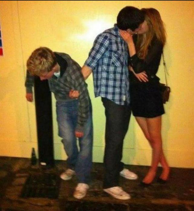 hombre besando a su novia sostiene a muchacho en otra sostiene a su amigo