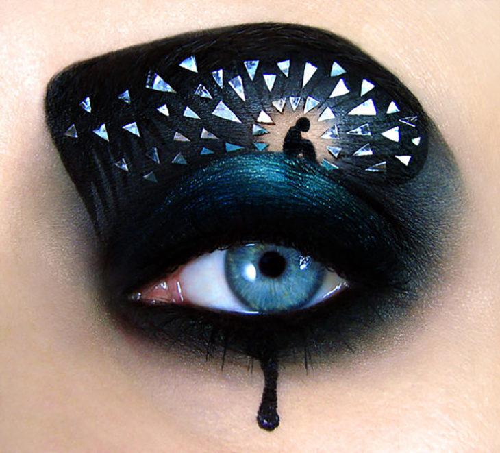 ojo maquillado con un monito hincado en soledad