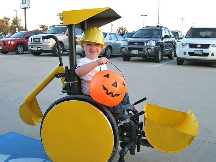 niño en silla de ruedas disfrazado de máquina excavadora
